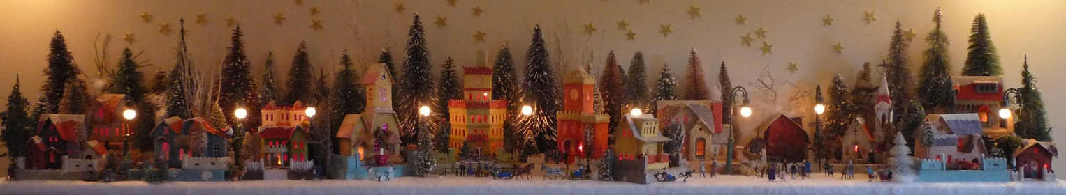 Antique Christmas cardboard house putz (village) on fireplace mantel at night (200K)